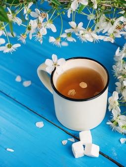 Xícara de chá primavera, flor de cerejeira sobre fundo azul de madeira