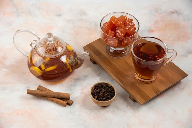 Xícara de chá quente, bule e geleia de marmelo doce na placa de madeira.