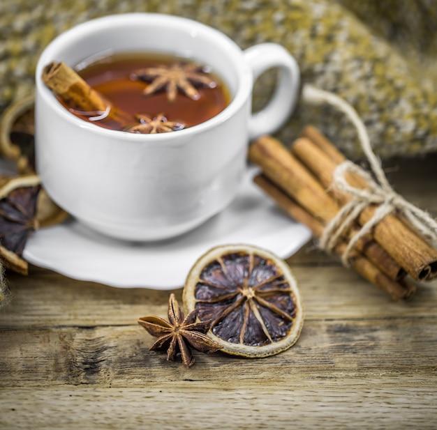 Xícara de chá quente com paus de canela e deliciosas frutas cítricas secas