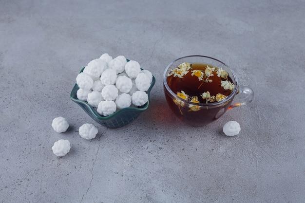 Xícara de chá quente com uma tigela branca de doces brancos na superfície da pedra.