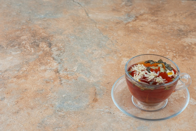 Xícara de chá quente de ervas no fundo de mármore