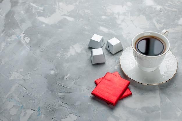 Xícara de chá quente dentro de uma xícara branca em uma placa de vidro com um pacote prateado de bombons de chocolate em uma mesa de luz, uma bebida de chá doce de chocolate na hora do chá