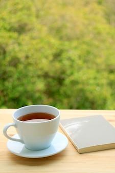 Xícara de chá quente e um livro em uma mesa ao ar livre com folhagem borrada