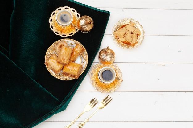 Xícara de chá quente e um prato de sobremesas turcas