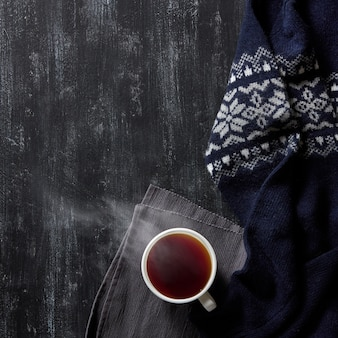 Xícara de chá quente em um fundo preto de madeira, blusa quente de inverno,
