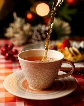 Xícara de chá quente perfumado em cima da mesa