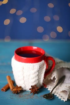 Xícara de chá quente saboroso na mesa de madeira no fundo brilhante