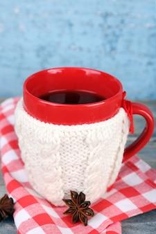 Xícara de chá quente saboroso, na mesa de madeira,