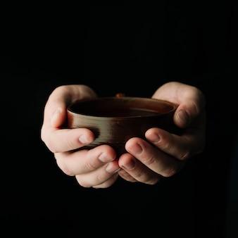 Xícara de chá quente, sendo realizada nas mãos