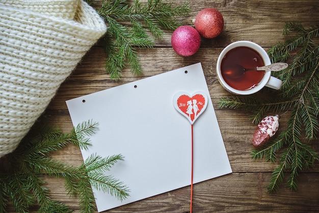 Xícara de chá, ramos de abeto, decorações de natal, um cachecol e uma folha de papel com um coração no palito