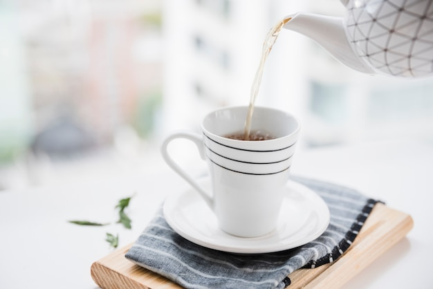 Xícara de chá sendo preenchida