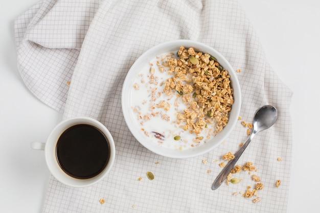 Xícara de chá; tigela de aveia; colher na toalha de mesa