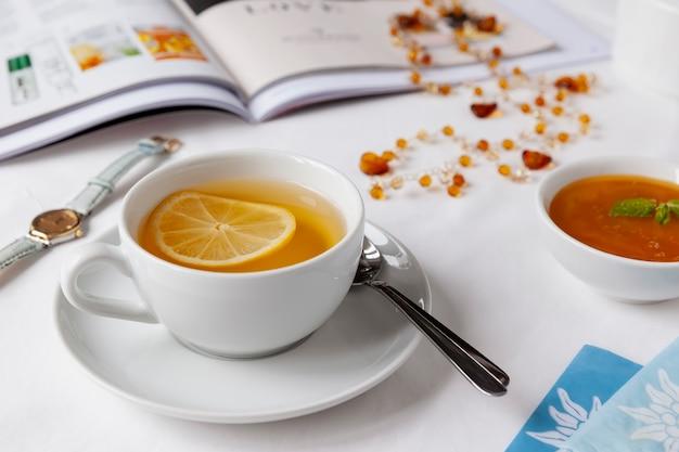 Xícara de chá verde branca com limão, mel e hortelã sobre um lençol branco com revista ilustrada, colar âmbar, relógio e saquinhos de chá. conceito saudável.