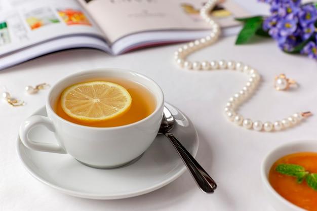 Xícara de chá verde branca com limão, mel e hortelã sobre um lençol branco com revista ilustrada, colar de pérolas, brincos e anel.