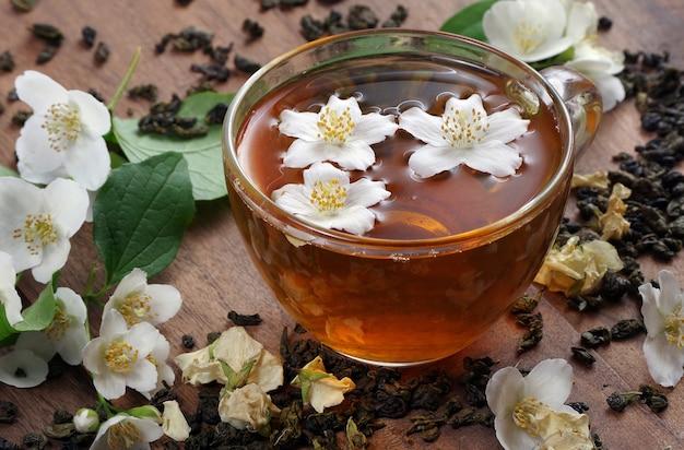 Xícara de chá verde com jasmim em uma mesa de madeira.
