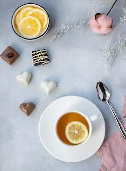 Xícara de chá verde com limão e sortidos deliciosos bombons de chocolate numa superfície cinza com flores. café da manhã de primavera.