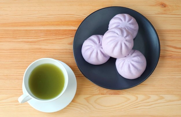 Xícara de chá verde com um prato de pãezinhos de taro cozido no vapor na mesa de madeira