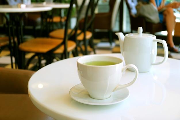 Xícara de chá verde e bule na mesa redonda branca em uma sala de chá
