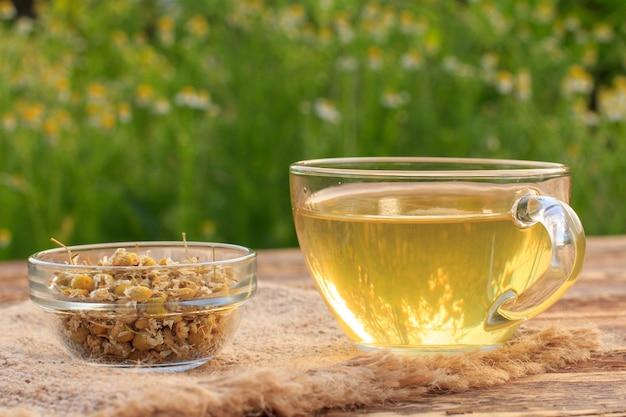 Xícara de chá verde e tigela de vidro com flores secas de matricaria chamomilla em placas de madeira com fundo verde natural.