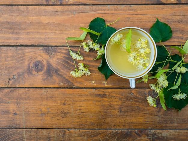 Xícara de chá verde e tília em fundo de madeira, conceito de medicina popular de flores de tília úteis