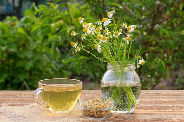 Xícara de chá verde, jarra com flores de camomila branca e pequena tigela de vidro com flores secas de matricaria chamomilla em placas de madeira com fundo verde natural.