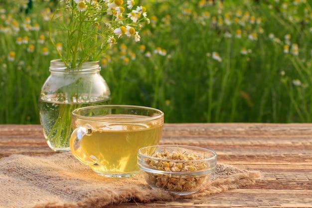 Xícara de chá verde, jarra com flores de camomila branca e tigela de vidro com flores secas de matricaria chamomilla em saco e tábuas de madeira com fundo verde natural.