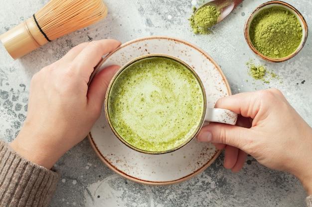 Xícara de chá verde matcha nas mãos da mulher.