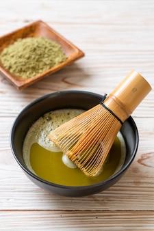 Xícara de chá verde matcha quente com chá verde em pó e bata