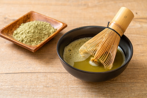 Xícara de chá verde matcha quente com pó de chá verde e bata