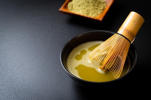 Xícara de chá verde matcha quente com pó de chá verde e batedor de bambu