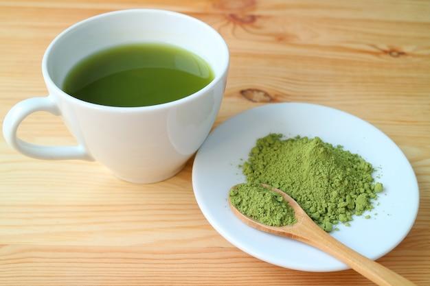 Xícara de chá verde matcha quente com um prato de chá em pó matcha na mesa de madeira