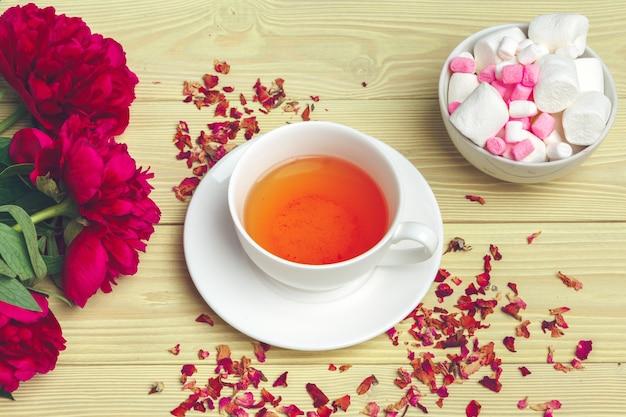Xícara de chá verde na mesa com flores de peônia fresca