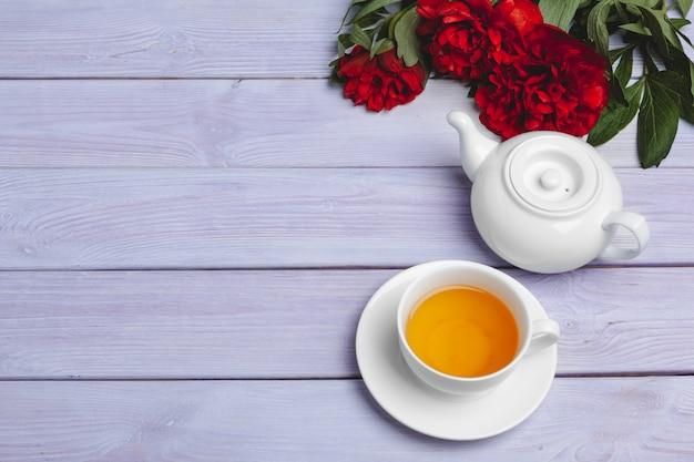 Xícara de chá verde na mesa com flores frescas de peônia