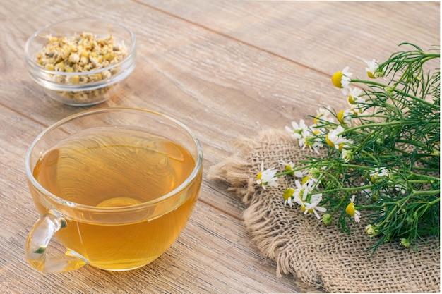 Xícara de chá verde, pequena tigela de vidro com flores secas de matricaria chamomilla e flores de camomila branca em pano de saco e fundo de madeira.