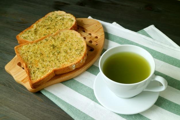 Xícara de chá verde quente com torradas de manteiga de alho no guardanapo branco e verde