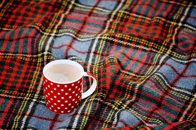 Xícara de chá vermelha pontilhada com chocolate quente em cobertor escocês conceito de casa aconchegante com caneca de porcelana vermelha