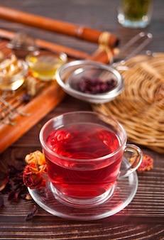 Xícara de chá vermelho de ervas com rosas secas de hibisco