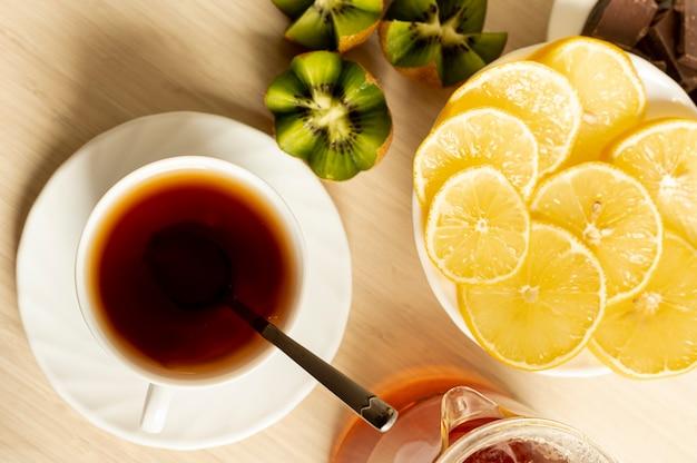 Xícara de chá vista superior com frutas no fundo liso