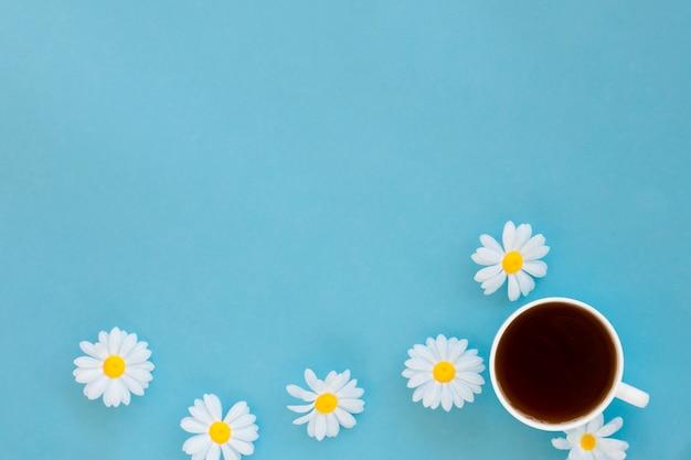 Xícara de chá vista superior, rodeada por flores, com espaço de cópia