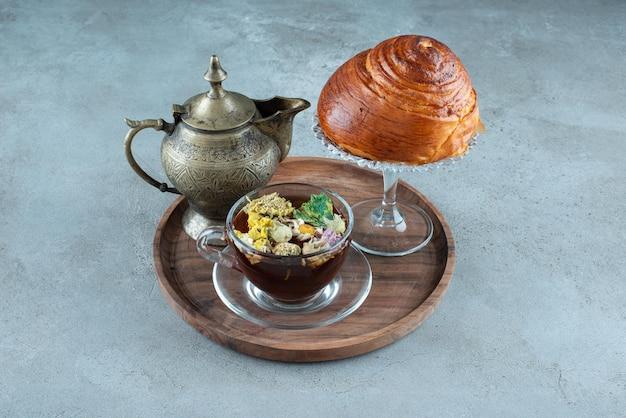 Xícara de chá, xícara de chá e pastelaria na placa de madeira.