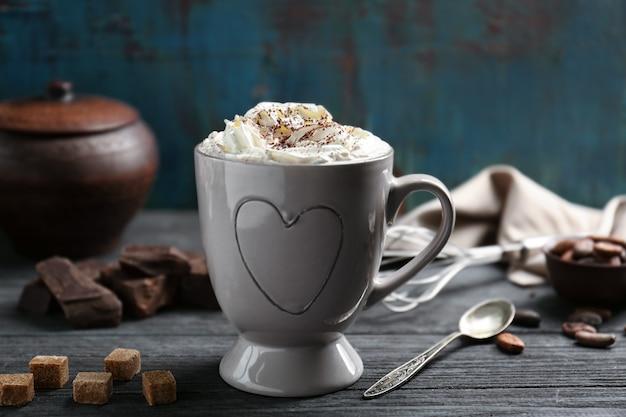 Xícara de chocolate com chantilly na mesa de madeira