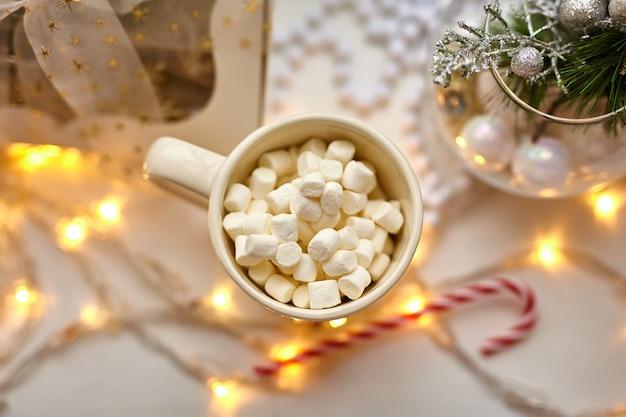 Xícara de chocolate com marshmallows, decorações de natal na mesa branca, bengala e caixa de presente