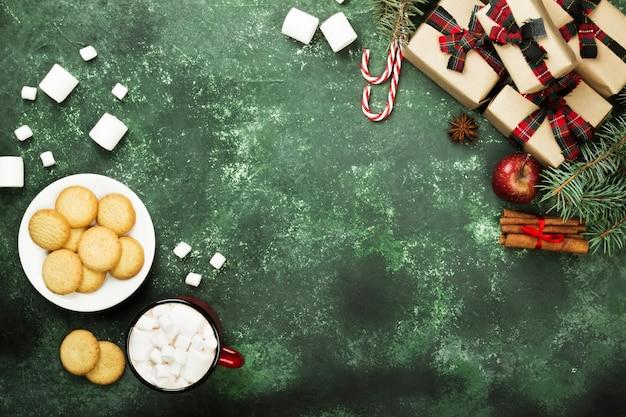 Xícara de chocolate quente, biscoitos e vários atributos de férias em uma superfície verde