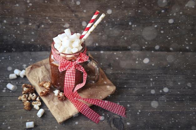 Xícara de chocolate quente, cacau com marshmallows e pipoca