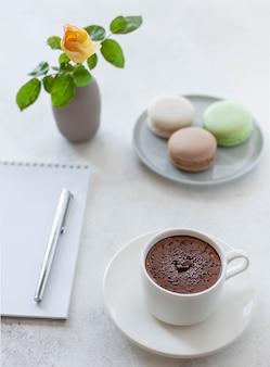 Xícara de chocolate quente com flores macarons e bloco de notas