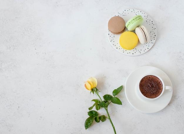 Xícara de chocolate quente com flores macarons