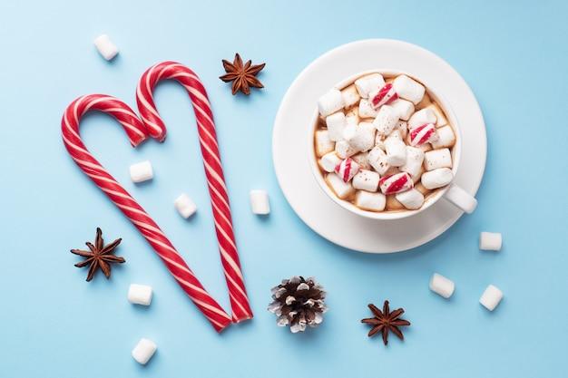 Xícara de chocolate quente com marshmallow cacau em pó e caramelo sobre fundo azul pastel com espaço de cópia. conceito de inverno natal.