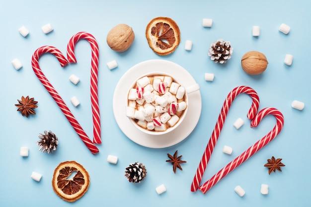Xícara de chocolate quente com marshmallow cacau em pó e nozes de caramelo, laranjas sobre fundo azul pastel com espaço de cópia. conceito de inverno natal.