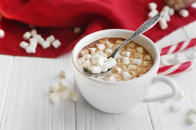 Xícara de chocolate quente com marshmallows e doces na mesa