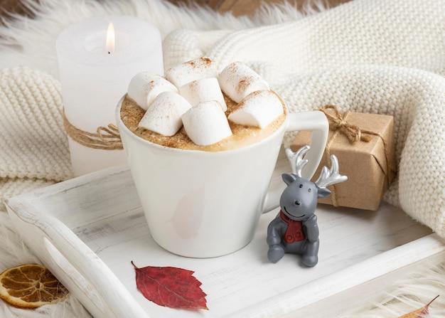 Xícara de chocolate quente com marshmallows e presente na bandeja